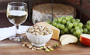 A table set with wine, cheese, pistachios, grapes and apples.