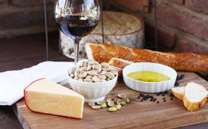 A table set with cheese, pistachios, wine, bread, and olive oil for dipping.
