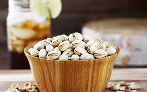 A wooden bowl filled with pistachios.